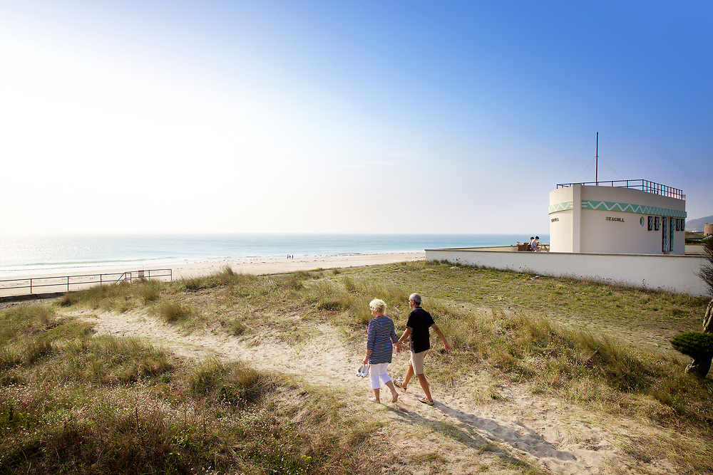 Couple walking through the sand dunes and pathway next to the Barge Aground, the beachfront Heritage accommodation at St Ouen's Bay