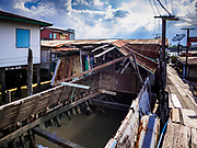"""20 JUNE 2017 - BANGKOK, THAILAND: An abandoned boat that used to be a home  in a community along the Chao Phraya River south of Krung Thon Bridge. This is one of the first parts of the riverbank that is scheduled to be redeveloped. The communities along the river don't know what's going to happen when the redevelopment starts. The Chao Phraya promenade is development project of parks, walkways and recreational areas on the Chao Phraya River between Pin Klao and Phra Nang Klao Bridges. The 14 kilometer long promenade will cost approximately 14 billion Baht (407 million US Dollars). The project involves the forced eviction of more than 200 communities of people who live along the river, a dozen riverfront  temples, several schools, and privately-owned piers on both sides of the Chao Phraya River. Construction is scheduled on the project is scheduled to start in early 2016. There has been very little public input on the planned redevelopment. The Thai government is also cracking down on homes built over the river, such homes are said to be in violation of the """"Navigation in Thai Waters Act."""" Owners face fines and the possibility that their homes will be torn down.              PHOTO BY JACK KURTZ"""