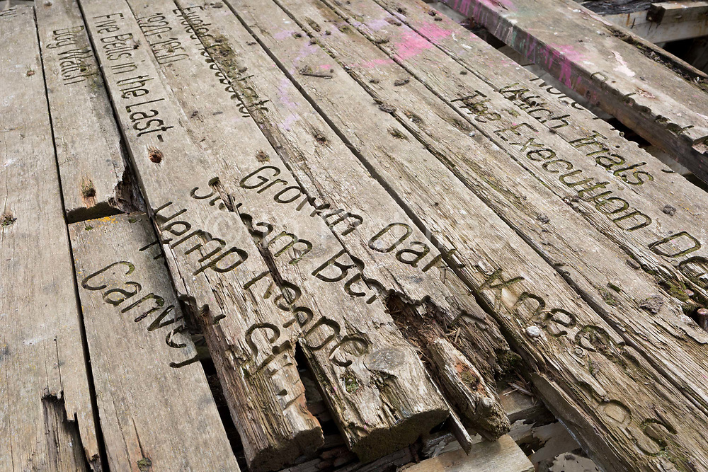 A detail of poetry and sentences forming Graveyard of Lost Species, a boat artwork created by by artists and commissioned by Arts Catalyst, at low-tide on the Thames estuary, at Leigh creek, on 10th September 2019, in Leigh-on-Sea, Essex, England. The project celebrates the local tradition of wrecking boats on the salt marsh, its decaying memory of what has changed or passed. The boat is the Souvenir, a 39-foot Thames bawley 1933 which once served the local fish trade in nearby Southend-on-Sea.