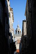Belltower and cupola of Saint Mark's Cathedral (Sveti Marko) viewed through narrow streets. Korcula old town, island of Korcula, Croatia.