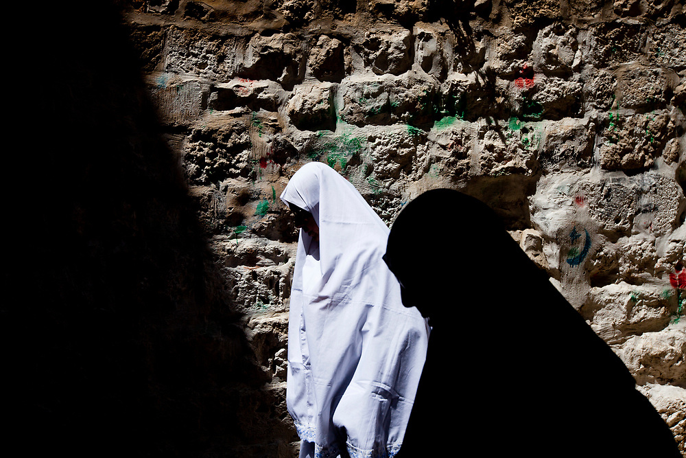 Palestinian women make their way through Jerusalem's Old City to attend prayers at the Al Aqsa Mosque on the second Friday of the Muslim holy month of Ramadan, August 20, 2010.
