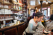 France, Paris, Young woman behind bar in the cafe La Marine