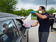 21 MAY 2020 - DES MOINES, IOWA: JASON ZILK hands a bag of meals to people in a drive through emergency food distribution in Evelyn K. Davis Park in central Des Moines. All of the 485 meals were distributed in about an hour. The economic fallout of the pandemic is being felt throughout Iowa. On May 21, 2020, Iowa reported that 187,375 people had filed for unemployment since the beginning of the COVID-19 pandemic and resulting economic shutdown. Emergency food pantry has also increased in that time, as many Iowans in low wage jobs used emergency food banks and pantries for the first time. The Food Bank of Iowa said Thursday that demand in April 2020 was 31% higher than demand in April 2019, mostly because of unemployment caused by the Coronavirus (SARS-CoV-2) pandemic. The emergency food distribution Thursday was organized by the city of Des Moines, Food Bank of Iowa, Central Iowa Shelter and Services, Urban Dreams and Orchestrate Hospitality.       PHOTO BY JACK KURTZ
