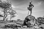 A portrait of a Samburu warrior standing on a rock, black and white,,Samburu, Kenya, Africa