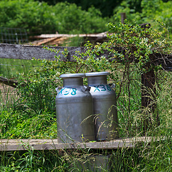 Bellville, PA, USA - May 23, 2013: Milk cans on a loading platform ready for pick up from an Amish farm in Kishacoquillas Valley in Mifflin County, PA.