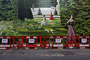 A background of hanging hoarding media, of a Dior shop being refurbished in central London. Barriers have been placed against the illustration that shows an incongruous <br /> fantasy garden with models placed around the landscape while construction work carries on in front and behind the screen. The Dior store occupies a prime location on one of London's most prestigious streets known for fashion and jewellery and work continues behind the screen, hidden to passers-by.