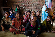 Chandrawati (center, in black), age unknown, sits on the floor amongst other rag-picker's children as they learn basic numerics in the Nai Duniya activity center in remote Lodha Basti, Manana village, Samalkha town, Haryana, India on 15th June 2012. Most of these children work as rag-pickers. They go to school from 8-12 in the morning, and study again at the activity center after work at 4pm. A new program to encourage the rag-picker's children to attend school is underway, to keep them from becoming the next generation of rag-pickers in cities. Photo by Suzanne Lee for The National