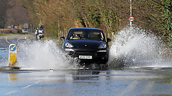 © Licensed to London News Pictures. 17/02/2014. Egham, UK. A car passes through floodwater. Fire And Rescue Services Set up pumps to clear the A308 Windsor Road near Runnymede. Photo credit : John Maxwell-Roberts/LNP