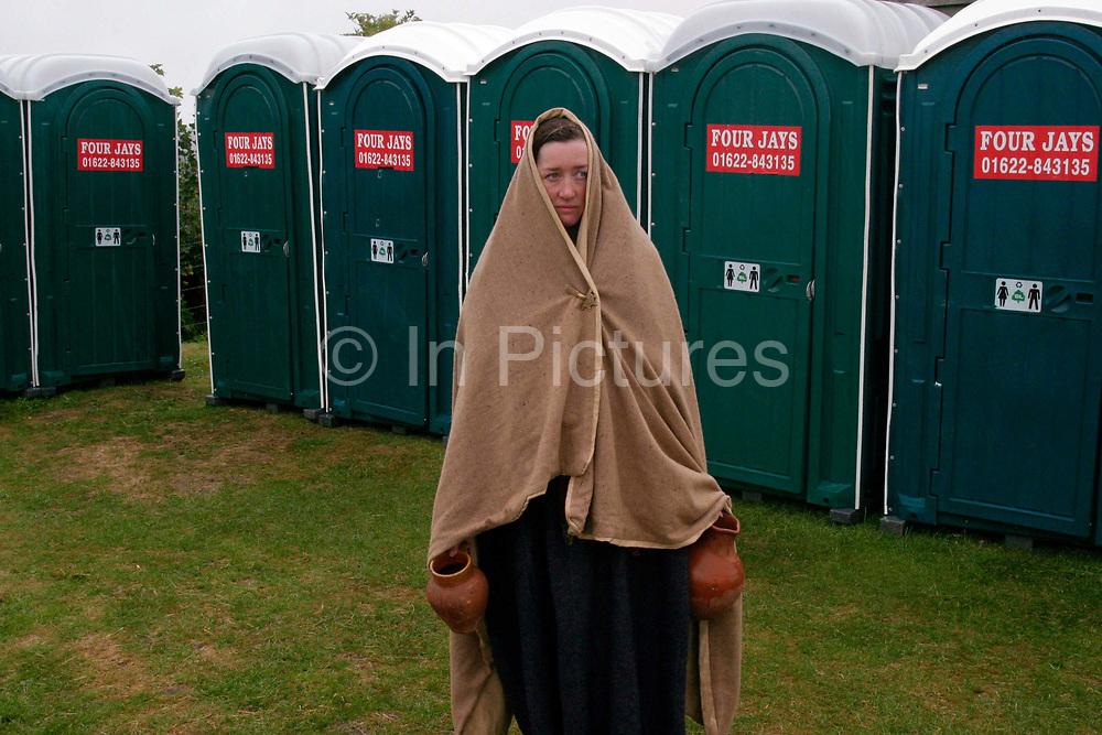 A member of the Roman re-enactment society waiting for a Portaloo at Richborough Roman Fort, Kent, UK