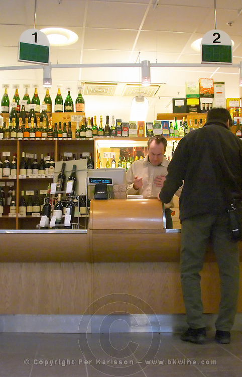 The customer counter in a traditional style Systembolaget shop the alcohol wine beer spirit monopoly retailer in Sweden. All bottles are asked for and delivered over the counter. A shop staff and a man in black buying a bottle. Stockholm, Sweden, Sverige, Europe