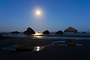 The full moon overs over the sea stacks at Bandon By The Sea on the southern Oregon Coast. The area's most famous sea stack, Face Rock, is visible on the horizon at the right side of the image. According to Indian legend, Face Rock is a tribe member who was turned to stone by an evil spirit who lives in the Pacific Ocean.