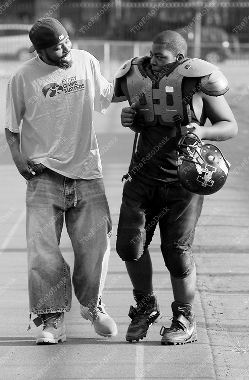 An African American male father with playing football. (Brian Branch Price)