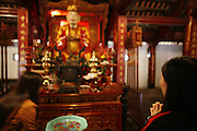 "Hanoi, Vietnam. March 11th 2007..A Vietnamese woman pray in the ""Van Mieu"", the Literature Temple"