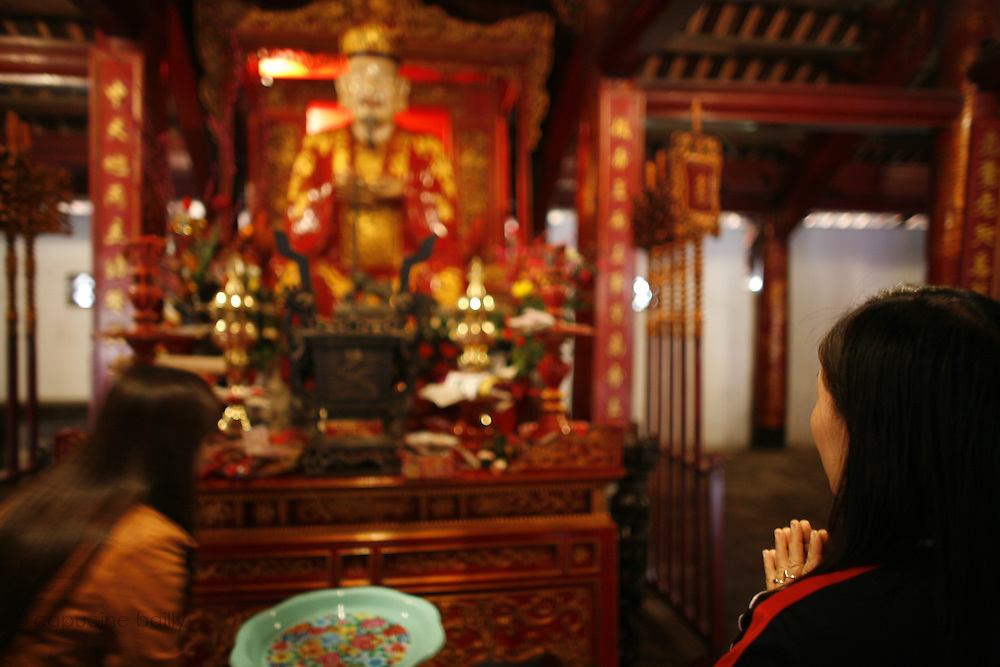 "Hanoi, Vietnam. March 11th 2007..A Vietnamese woman pray in the ""Van Mieu"", the Literature Temple"