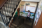A Nepalese man walks across the stairwell of the Voice of Children rehabilitation center in Kathmandu, Nepal.  The not-for-profit organisation supports street children and those who are at risk of sexual abuse through educational and vocational training opportunities, health services and psychosocial counseling.