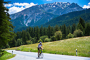 Cycling uphill in the Swiss National Park with background of the Swiss Alps, Switzerland