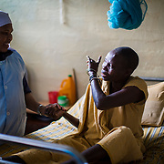 A nun who works as a nurse at the Ifakara Leprosarium talks to one of the patients.