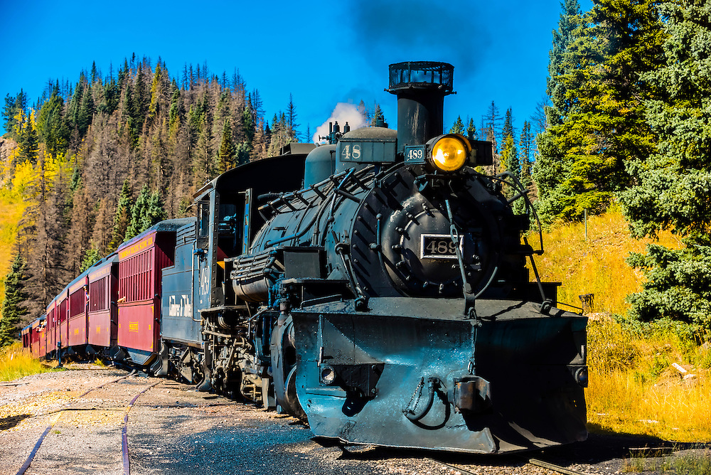 The Cumbres & Toltec Scenic Railroad train pulled by a steam locomotive on the 64 mile run between Chama, New Mexico and Antonito, Colorado takes on water for the boiler, near Cumbres Pass. The railroad is the highest and longest narrow gauge steam railroad in the United States with a track length of 64 miles. The train traverses the border between Colorado and New Mexico, crossing back and forth between the two states 11 times. The narrow gauge track is 3 feet wide. It runs over 10,015 ft (3,053 m) Cumbres Pass.