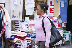Woman out shopping passing a soft furnishings shop,