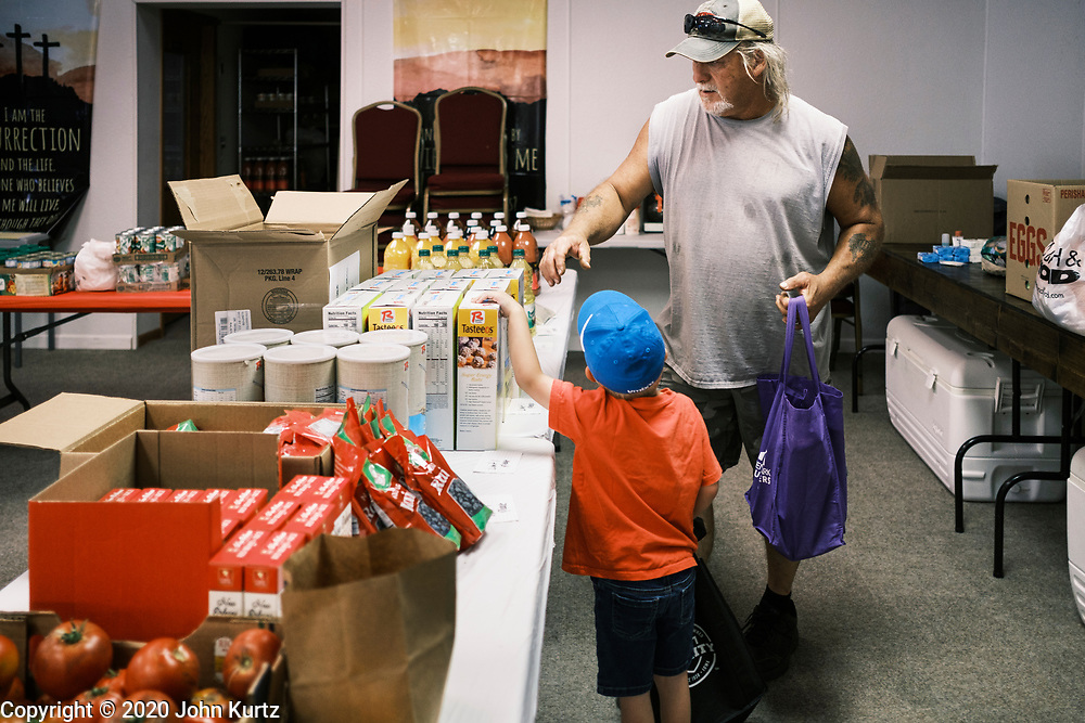 "16 SEPTEMBER 2020 - MITCHELLVILLE, IOWA: A man and his son look for cereal in the pantry at the Heritage Word of Life Church. There is no grocery store in Mitchellville, a small community in eastern Polk County. It doesn't qualify as a ""food desert"" under USDA guidelines because there are grocery stores within 10 miles in neighboring communities, but based on state data, Mitchellville is the poorest community in Polk County (which includes the Des Moines metropolitan area). The Mitchellville zip code has the lowest per capita income in Polk County. Many people don't own cars and can't get to neighboring communities to buy groceries. The library in Mitchellville has made arrangements with a neighboring community to serve hot meals. Every day someone from the Mitchellville library picks up hot meals from a nearby town and distributes them in the library. Heritage Word of Life, a church across the street from Library, has a food pantry in their Fellowship Room where people can pick up fresh vegetables, staples, and hygiene needs.       PHOTO BY JACK KURTZ"