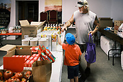 """16 SEPTEMBER 2020 - MITCHELLVILLE, IOWA: A man and his son look for cereal in the pantry at the Heritage Word of Life Church. There is no grocery store in Mitchellville, a small community in eastern Polk County. It doesn't qualify as a """"food desert"""" under USDA guidelines because there are grocery stores within 10 miles in neighboring communities, but based on state data, Mitchellville is the poorest community in Polk County (which includes the Des Moines metropolitan area). The Mitchellville zip code has the lowest per capita income in Polk County. Many people don't own cars and can't get to neighboring communities to buy groceries. The library in Mitchellville has made arrangements with a neighboring community to serve hot meals. Every day someone from the Mitchellville library picks up hot meals from a nearby town and distributes them in the library. Heritage Word of Life, a church across the street from Library, has a food pantry in their Fellowship Room where people can pick up fresh vegetables, staples, and hygiene needs.       PHOTO BY JACK KURTZ"""