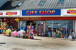 """A traditional Sea front Gift Shop with one of the rapidly disappearing """"1 Hour Photos"""" signs displays its main products of Buckets Spades and Beach ball  on Cobble Landing at Filey North Yorkshire<br /> <br /> 21 May 2013<br /> Image © Paul David Drabble<br /> www.pauldaviddrabble.co.uk"""