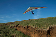 Hang glider takes off above signs of coastal soil erosion on the south side of the Isle of Wight, United Kingdom. This eroded landscape is fast approaching the coast road which links the east of the island with the west. There is currently no provision or plan to sure up the area or move the road.(photo by Mike Kemp/In Pictures via Getty Images)
