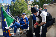 A pro remain protester speaks with a police officer outside the Cabinet office in Whitehall, London, United Kingdom on 22nd August 2019. Inside ministers are discussing Brexit at a daily Brexit Cabinet Meeting.