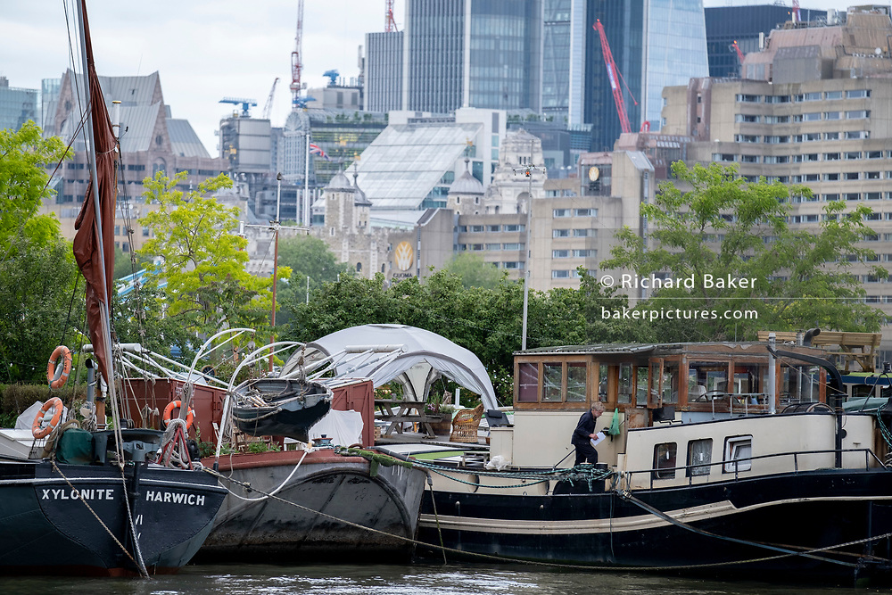 With the capital's financial district inthe background, barges and lighters at Tower Bridge Moorings are grouped together on the river Thames, on 11th June 2021, in London, England. 'Xylonite' is one of seven Thames barges built between 1925 and 1930. Tower Bridge Moorings is the capital's only floating gardens - a sustainable way of living for a community of more than one hundred adults and children, and a shelter for wildlife on the river. Tower Bridge Moorings is the capital's only floating gardens - a sustainable way of living for a community of more than one hundred adults and children, and a shelter for wildlife on the river.