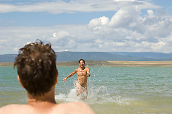 Man sitting on a lakeshore watching a naked man run playfully out of the lake
