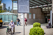A warning sign explaining social distance on a square and a begging woman from Bosnia infront of a shopping center in Bad Homburg which is a spa city close to the Taunus mountain range.