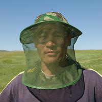 "MONGOLIA.  Mongolian archaeology student, Batjargal Khadbaatar (""Khada"") in a bug hat to keep away swarming gnats and insects."