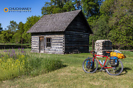 Bicycle touring along the Sheyenne Scenic Byway with Historic Wadeson Homestead Cabin in southeastern North Dakota, USA