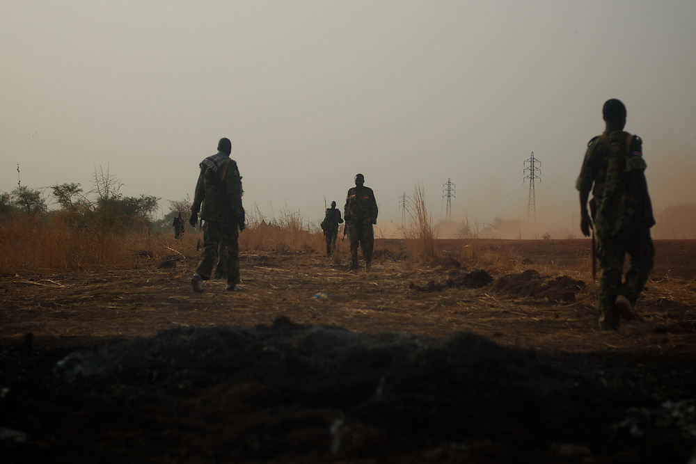 April 24, 2012 - Panakuach, South Sudan: A group of SPLA soldiers passes by the scene where a bomb dropped by the SAF air force landed minutes earlier near the last defensive line outside the village of Panakuach, 70 kilometers north of Bentiu...South Sudan and their northern neighbors, Sudan, have in the past two weeks been involved in heavily clashes over border disputes. Bentiu and neighboring villages have been under constant bombardment by the troops os Karthoum , who established their positions around 10 kilometers into South Sudan's territory. The international community is concerned about the possibility of a full on war between the two countries. (Paulo Nunes dos Santos/Polaris)