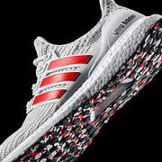 White Adidas Ultra Boost 4.0 with red stripes and multi-color pattern Continental sole.