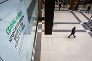 A man walks underneath a government health warning poster on the concourse of Liverpool Street Station in what would normally be the rush hour in the City of London on March 17th, 2020. The financial district of the UK is unusually quiet after the government requested people to refrain from all but essential travel and activities yesterday.