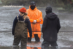 Denham, UK. 8th December, 2020. HS2 security guards form a line across the River Colne during a large security operation to remove Dan Hooper, widely known as Swampy during the 1990s, from a bamboo tripod. The climate and roads activist had occupied the tripod the previous day in order to delay the building of a bridge as part of works for the controversial HS2 high-speed rail link.