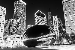 """Cloud Gate Chicago Bean black and white picture at night. Frequently called """"The Bean"""" for its bean shape,  Cloud Gate was created by Anish Kapoor and is located in Millennium Park in Grant Park in the downtown Chicago Loop."""