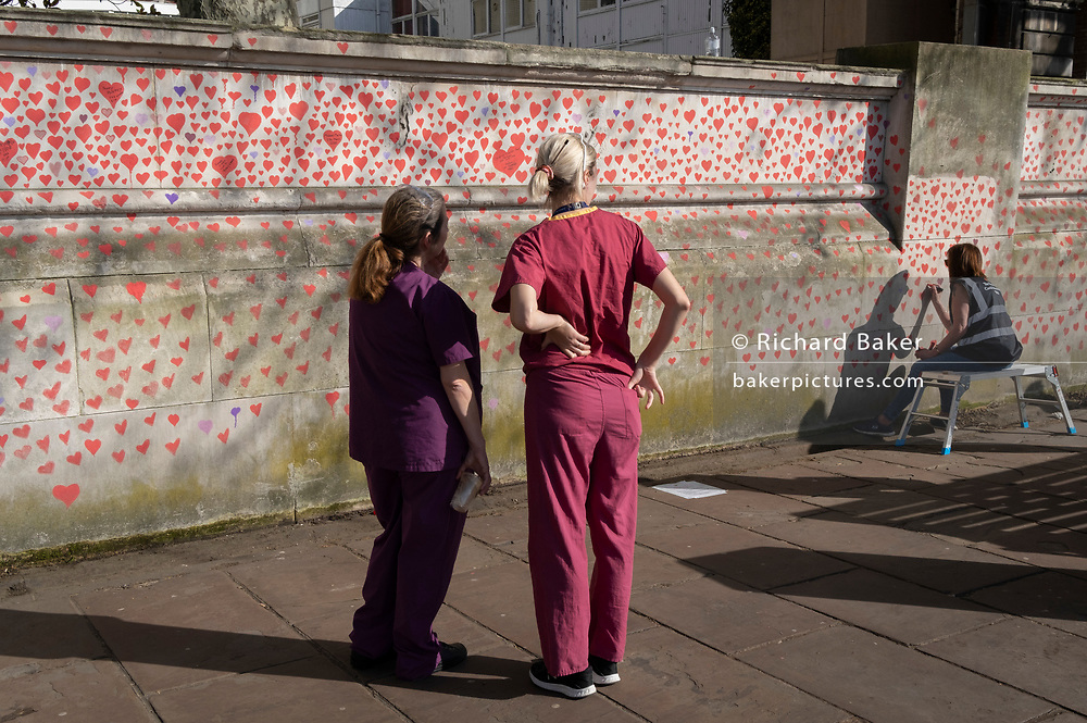 NHS staff look at the red hearts that forms the National Covid Memorial Wall, a tribute to the 150,000-plus British victims of the Coronavirus pandemic. Bereaved family and friends of Covid-19 victims have started working on the wall located outside St Thomas' Hospital, and which faces the Houses of Parliament in Westminster, on 30th March 2021, in London, England. Prime Minister Boris Johnson was treated for Covid at St Thomas' last year.