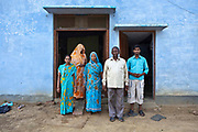 A farmhouse and its family in the village of Bagabar in the Maharai district of India. The covered daughter in the background it recently married so does not not her face to strangers.