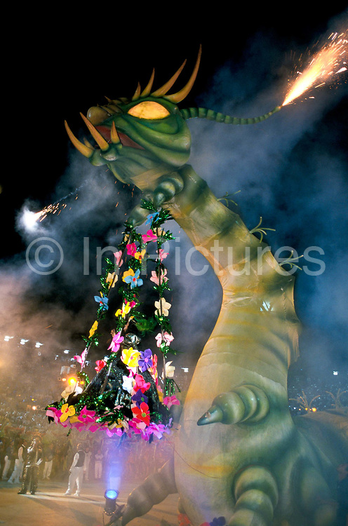 """A oversized Caterpiller enters the """"Bumbodromo"""", the stadium where the """"Boi Bumba"""" Carnival takes place, Parintins, Brazil. The carnival serves to celebrate and re-enact Indian traditions and perpetuate myths and legends. It has evolved over time and involves the battle between to opposing bulls, known as Garantido and Caprichoso."""
