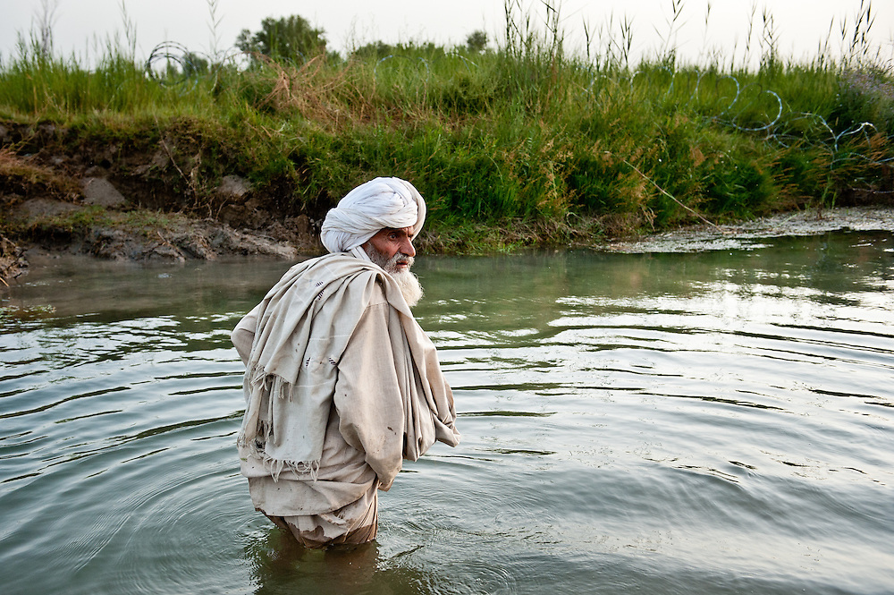 An elderly villager crosses an irrigation creek on his way to PB Fires after being detained.
