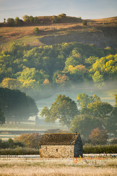 A crumbling stone barn sits under a backdrop of morning mist and colourful autumn trees, in the Hope Valley. A seasonal landscape scene in the Derbyshire Peak District, England, UK.