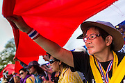 """09 MAY 2014 - BANGKOK, THAILAND: Thai anti-government protestors carry a huge Thai flag through the streets near Government House in Bangkok. Thousands of Thai anti-government protestors took to the streets of Bangkok Friday to start their """"final push"""" to bring the popularly elected of government of Yingluck Shinawatra. Yingluck has already been forced out by a recent court ruling that forced her to resign and she is facing indictment by the National Anti Corruption Commission of Thailand for alleged improprieties related to a government rice price support scheme. The protestors Friday were marching to demand that she not be allowed to return to politics. The courts have not banned her party, Pheu Thai, which has formed an interim caretaker government to govern until elections expected in July, 2014. Suthep Thaugsuban, secretary-general of the People's Democratic Reform Committee (PDRC),  said the president of the Supreme Court and the new senate speaker, who would be selected Friday, should set up an """"interim people's government and legislative assembly."""" He went onto say that if they didn't, he would.     PHOTO BY JACK KURTZ"""
