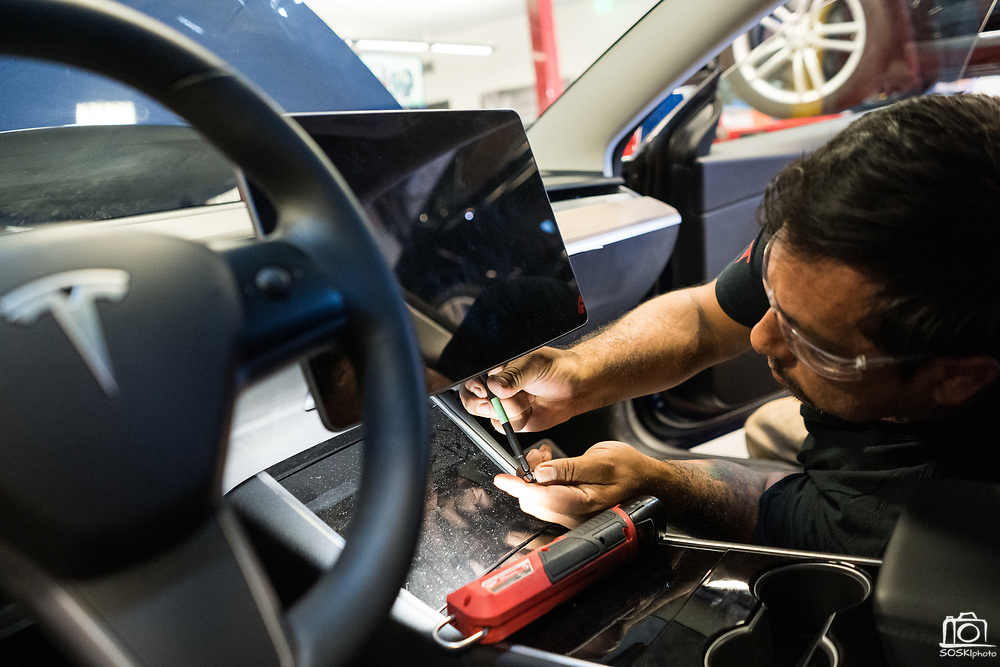 Raymond Ortega of Merced installs a Tesla Model 3 display unit during the Tesla Start class at Evergreen Valley Community College in San Jose, California, on August 8, 2019. (Stan Olszewski for Silicon Valley Business Journal)