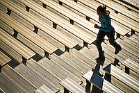 A young woman runs up a set of bleacher stairs during training.