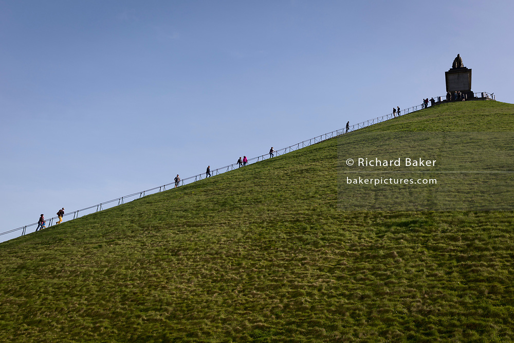 Visitors climb and descend the 225 steps, 43 metre high Waterloo Lion's battlefield Mound, on 25th March 2017, at Waterloo, Belgium. The Lion's Mound (Butte du Lion is a large conical artificial hill completed in 1826. It commemorates the location on the battlefield of Waterloo where a musket ball hit the shoulder of William II of the Netherlands (the Prince of Orange) and knocked him from his horse during the battle. From the summit, the hill offers a 360 degree vista of the battlefield. The Battle of Waterloo was fought 18 June 1815. A French army under Napoleon Bonaparte was defeated by two of the armies of the Seventh Coalition: an Anglo-led Allied army under the command of the Duke of Wellington, and a Prussian army under the command of Gebhard Leberecht von Blücher, resulting in 41,000 casualties.