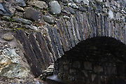 Detail of an arched stone bridge at Kinlochspelve, Isle of Mull, Scotland. The close-up view shows us the bridge's strength largely given by the beautiful workmanship by those using local materials for this road overpass. Only farm vehicles and small cars generally drive over but such structures need to withstand harsh winters where weather can help them deteriorate. An arch is a structure that spans a space and supports a load. Arches appeared as early as the 2nd millennium BC in Mesopotamian brick architecture and their systematic use started with the Ancient Romans who were the first to apply the technique to a wide range of structures.