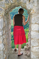 Single German Female tourist in red dress looking out window or ruins of German castle