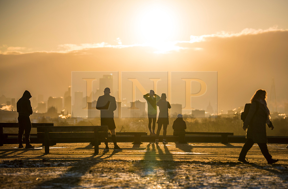© Licensed to London News Pictures. 10/02/2021. London, UK. Members of the public watch as the sun rises over the city of London, as seen from Primrose Hill in Camden, north London, on another morning of sub zero temperatures in the capital. Photo credit: Ben Cawthra/LNP